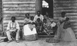 Enslaved adults, children, and babies sitting in front of slave cabin