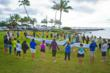 Friends and employees of Parrish Kauai circle around their new outrigger canoe.
