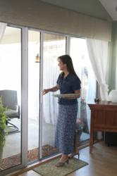 Photograph of the Plisse retractable screen in use on a sliding glass door.
