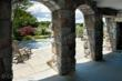 Stone arched pass-through to jacuzzi and pool area.