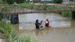 Jonathan Aubuchon working in the field gathering data in a river. He and a coworker standing in the middle of the river.