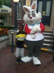 pictures, an African american child poses with a white rabbit at Disneyland