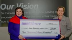 Mentoring Minds employee, Connie Moore, presents MindSHARE award to Amy Baskin, Executive Director at Young Audiences of Northeast Texas
