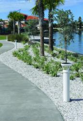 A row of white-colored, solar-powered lighting bollards line a walkway that runs near a lake