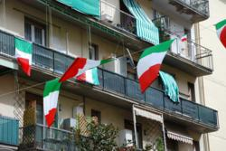 Picture of an apartment building in Italy with flags out for March 17th