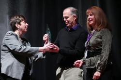 Tina Soika, AHAA President, hands John Miles, Au.D. and Janet Snyder-Miles, Au.D., their award at AHAA's 2013 Convention in Las Vegas.