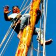 Author Allen Taube climbs up the mast on his schooner Reef Chief.