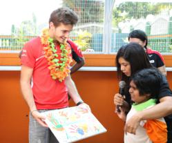 Marussia F1 Team Driver, Jules Bianchi, receives handprint art made by a child at the Taarana School