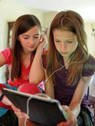 Two young girls with dyslexia share earbuds while listening to a Learning Ally audiobook on the iPad
