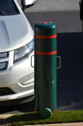 A Reliance Foundry plastic post cover that has been modified into an electric car charging station is shown at the edge of a parking space