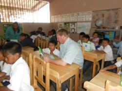 Greg Ubert works with children at new computer desks donated by Crimson Cup Coffee & Tea.