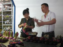 Winnie inspects high heel shoes at shoe factory in China