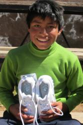 Mauricio from Peru displays his new shoes from Buckner International's Shoes for Orphan Souls.