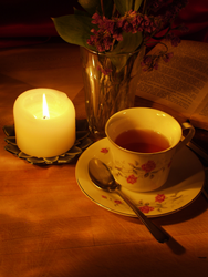 A tea cup warmly lit by a candle.