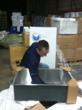 Chris Breen of VIGO prepares the kitchen sinks for the charitable donation to CRM.