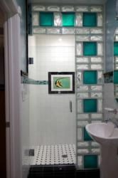 Glass block shower wall using colored 8 x 8 glass blocks and 4 x 8 wave blocks for style