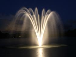An Arbrux fountain lit at night, featuring an Arbrux submersible lighting kit.