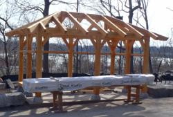 The timber frame pavilion, crafted and raised by New Energy Works Timberframers, offers patrons of the Niagara Falls Scenic Trolley shelter and a place to rest.