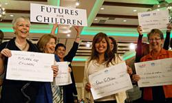 Futures for Children President/CEO, Teresa C. Gomez (holding FFC sign) surrounded by supporters displaying their $500 grant checks.
