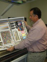 "Sean Johnson, Director of Manufacturing and Print Technology for Tattoo Manufacturing International, displays the ""final exam"" for the G7 Master Print Designation awarded by the IDEAlliance."