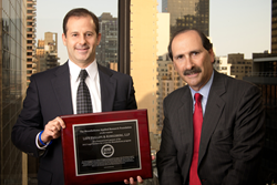 LPK partners Jerome H. Block (left) and Robert I. Komitor (right) holding a plaque signifying the firm's top-level sponsorship of the Mesothelioma Applied Research Foundation.