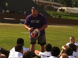 FCA Football Director Scott Pope pictured with young athletes at summer football camp