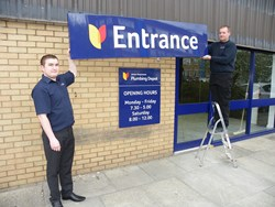 Branch Manager Simon Waite, with Paul Ducwra, putting up the Entrance Sign at Plumbing Depot Shipley