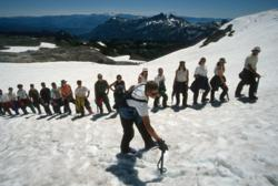 Wilderness Ventures teen summer camp hiking up a snowy mountain.