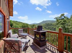 Showcasing the patio of Cabin Fever Vacation's Smoky Seasons cabin, this picture has three plus deck chair angled around a relaxing fire pit overlooking the mountains in the distance.