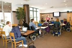 A classroom filled with people in wheelchairs and assistive devices being instructed by Lynn Wehrman