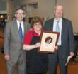 "nterim MU President Allan Golden and Director of DIning Services Drew Robinson present Maraget ""Fuzzy"" Horton with a portrait of herself taken when she started at Mansfield in 1948."