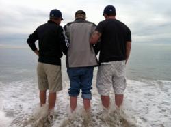 Bill Kransky stepping into the Pacific Ocean with his lawyers, Dean Goetz and John Gomez at his side.