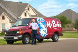 mr rooter technician in front of company van