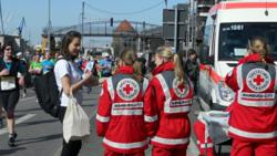 Volunteer from the Church of Scientology Hamburg hands a copy of The Way to Happiness to ambulance workers on duty at the Hamburg Marathon April 21.