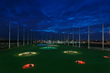 TopGolf outfield with targets lit up at night for point-scoring golf games