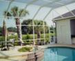 A swimming pool enclosure from Venetian Builders, Inc.: The bugs stay away while the homeowners play.