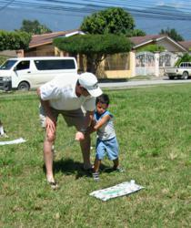 Image of Gabelmann teaching one of the orphaned children about the golf swing