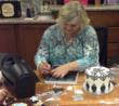 Stacey Caron, President of Spellbinders, works with new dies for the Spellbinders Sweet Accent cake designing machine.