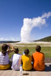 Children sit breathless as Yellowstone's Old Faithful energizes the landscape part of a WOW! Factor moment organized by Austin Lehman adventures..