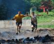 The finish of the race involved climbing over an 8 foot wall and then jumping over a fire pit. Dr. Michael Cocilovo is on the right.