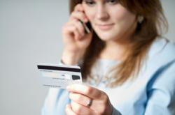 A woman making a telephone payment using her credit card