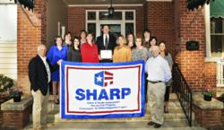 picture of raleigh comprehensive and cosmetic dentistry being presented with sharp award from ncdol