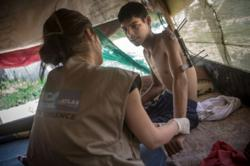 Abeer, a physiotherapist for Handicap International, gives a post-operative physical therapy session to Faraj, 16. Faraj is a Syrian refugee and was wounded in Syria during a bombardment.