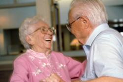 Two senior citizens (one male and one female) are happily dancing together at a Carlton Senior Living Community.