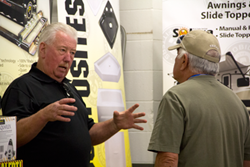 Sonny Dismuke in LCI product development talks with a customer on June 19 at the North American Heartland Owners Club Rally in Goshen, Ind.