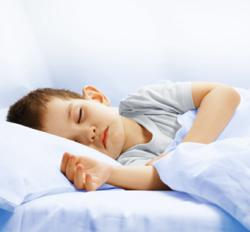 Child sleeping peacefully on pillow in bed