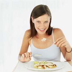 Young woman eating fish