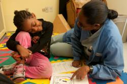 Michelle Morgan-Jackson reads with a patient at The Floating Hospital