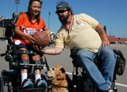 Veteran in  wheelchair hands basketball to child in wheelchair
