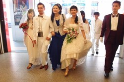 Above: With brides and grooms in hand, a happy matchmaker Hellen Chen (Center) strides forward with the message that believing in love again can heal broken hearts.